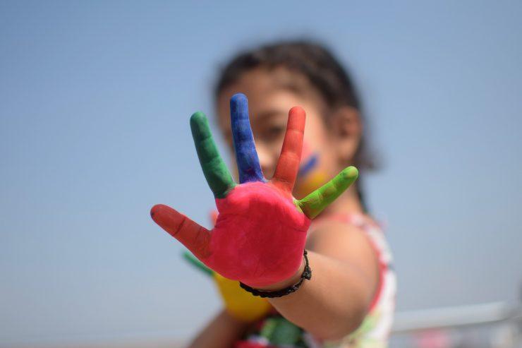 Foto de menina com as mãos pintadas. A palma, vermelha, está em evidência.