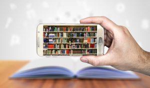 Uma mão segura um smartphone, que aponta a câmera para um livro aberto. Na tela, a imagem de centenas de livros em uma biblioteca