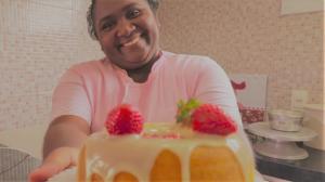Iolanda Galvão segura um bolo confeitado com morangos e sorri para a câmera. Ela é uma mulher negra, com roupa rosa e traja uma touca na cabeça.