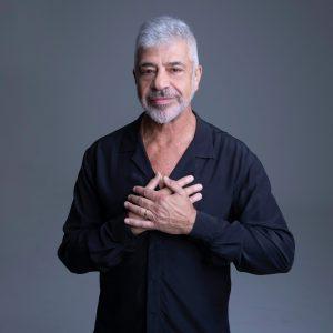 Foto do cantor Lulu Santos. Ele usa uma blusa preta e faz um sinal sobre o coração.
