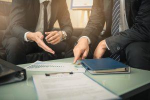 A imagem mostra dois homens conversando, mas não aparecem suas cabeças. O foco são suas mãos e ambos trajam ternos. Sobre a mesa em que discutem, há papéis e relatórios. Ilustra os sindicatos patronais