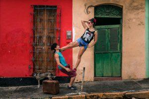 Um homem e uma mulher fazem uma apresentação em frente a uma casa. Ele está agachado e ela se apoia em seu tronco e pernas.
