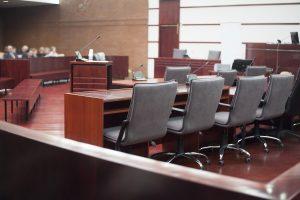 Sala jurídica. Várias cadeiras estão dispostas na sala, com mesas e microfones. Ilustra o espaço das varas empresariais