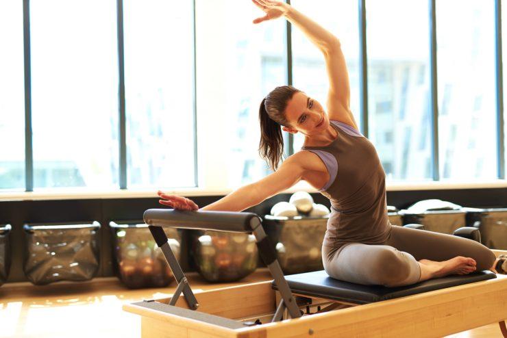 Mulher branca, de cabelo castanho e rabo de cavalo, pratica um exercício de pilates. Ela traja um body cor cinza.