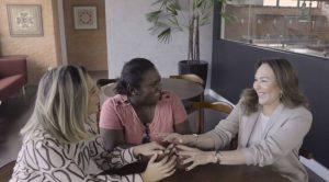 Três mulheres conversam e juntam as mãos em uma mesa. A da esquerda é branca e possui mechas loiras no cabelo. Ao centro, uma mulher negra e com camisa rosa. À esquerda, uma mulher branca de cabelo castanho e blazer cinza.