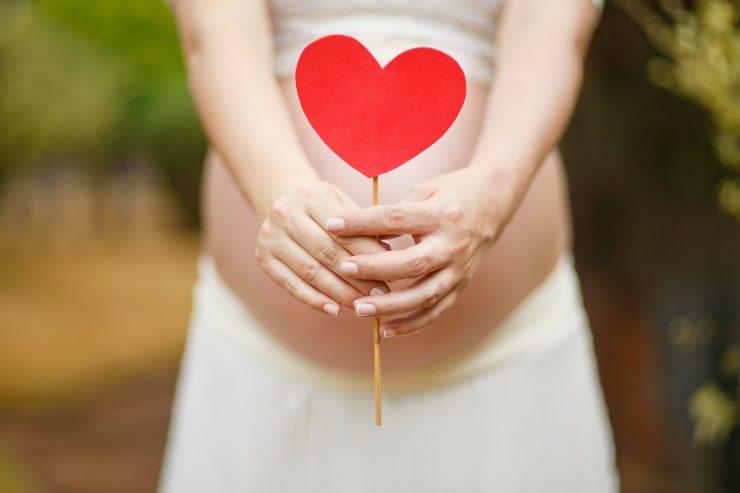 Gestante segurando coração de papel em frente à própria barriga; gestantes e bebês enfrentam desafios nesta pandemia
