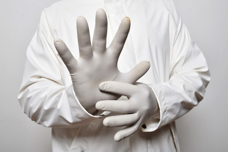 Pessoa com luvas cirúrgicas e batas,proteção necessário aos profissionais da saúde