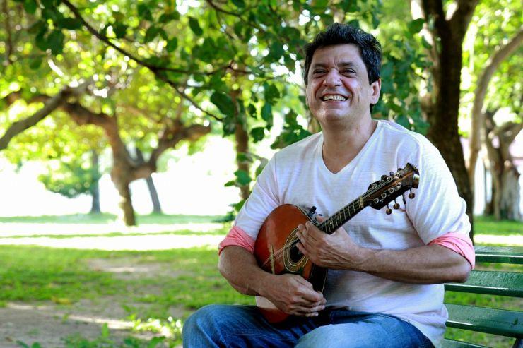 Carlinhos Patriolino sentado em um banco de praça, com seu bandolim