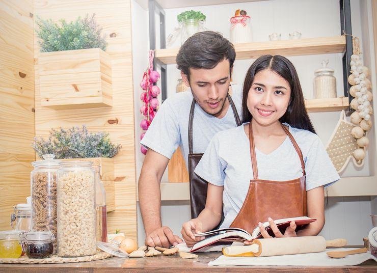 Rapaz e moça abrindo livro de receita em cozinha; confira dicas para o Dia dos Namorados