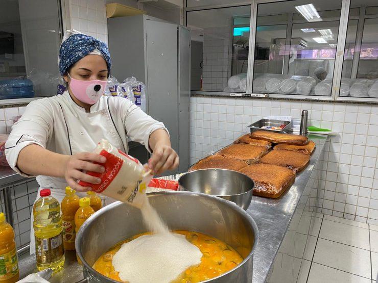 Mulher preparando comida na cozinha do Senac para ação solidária