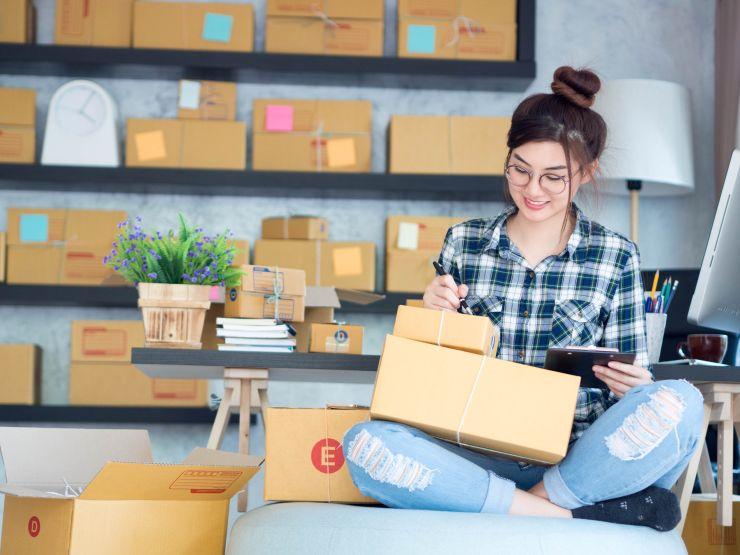 Mulher segurando caixas de papelão; pós-pandemia exige adaptação ao novo mercado
