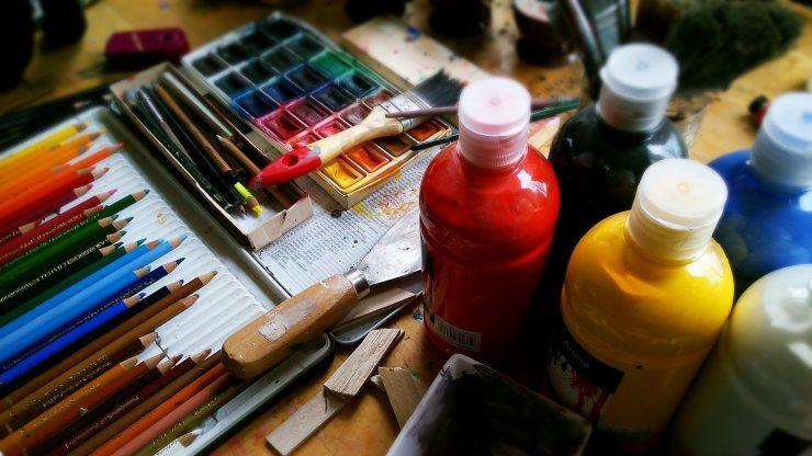 Materiais de pintura, como tinta, pincéis e lápis, em cima de uma mesa; Sesc oferta programação de cursos de artes