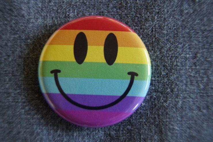 Butoon com carinha feliz desenhada, nas cores da bandeira LGBT; diversidade sexual é tema de debates e lives do Sesc