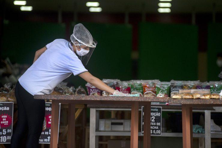 Mulher limpando mesa de um dos negócios locais da Cidade