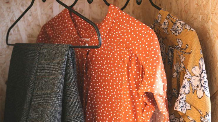 Cabides com blusas e calça, representando um guarda-roupa cápsula