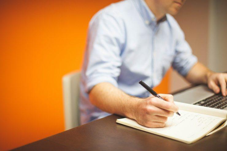 Na foto, há um homem com uma camisa social azul com as mangas dobradas no cotovelo. Ele segura um lápis e faz anotações em um caderno com folhas brancas, em cima de uma mesa marrom. Não vemos o seu rosto. Ele está sentado em uma cadeira branca em frente à uma parede laranja.