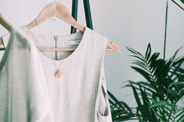 Na foto, há uma camisa sem mangas na cor branco cru pendurada em um cabide de madeira bege. Junto à camisa, há um colar dourado com um pingente em forma de moeda. Atrás do cabide e da camisa, há uma parede branca e à direita, uma planta.