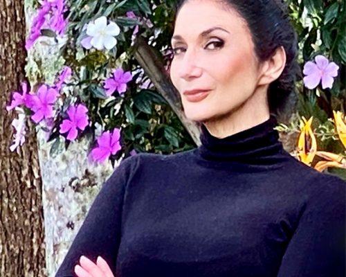 Na foto, Zizi Possi usa uma blusa preta e justa de gola alta, está com os braços cruzados e o cabelo escuro preso em um coque. Ela sorri para a câmera e está em frente a um muro com flores roxas.