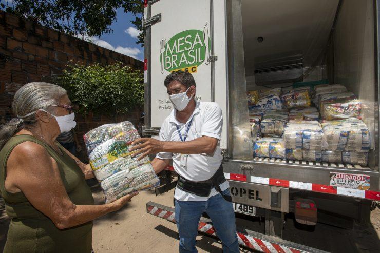 Homem de máscara entregando pacotes de comida a uma senhora idosa, também de máscara; programa de solidariedade do Mesa Brasil Sesc beneficiou  quilombolas, indígenas, ciganos e população de terreiros