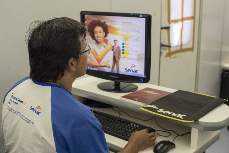 Rapaz em frente a um computador, acessando página de cursos gratuitos