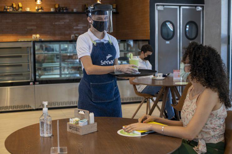 Homem serve uma cliente, utilizando máscara de proteção; cursos gratuitos na área de varejo e restaurantes são ofertados
