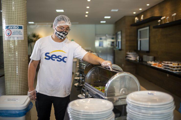 Homem com blusa do Sesc, de máscara e touca, abrindo tampa de sel-service; trabalhadores do comércio podem acessar serviços do Sesc