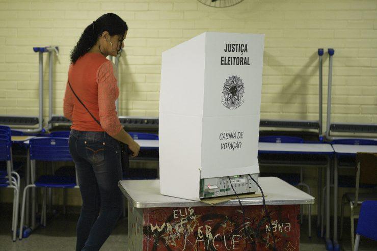 Mulher chegando para votar em urna eletrônica; candidatos são entrevistados em série da Fecomércio