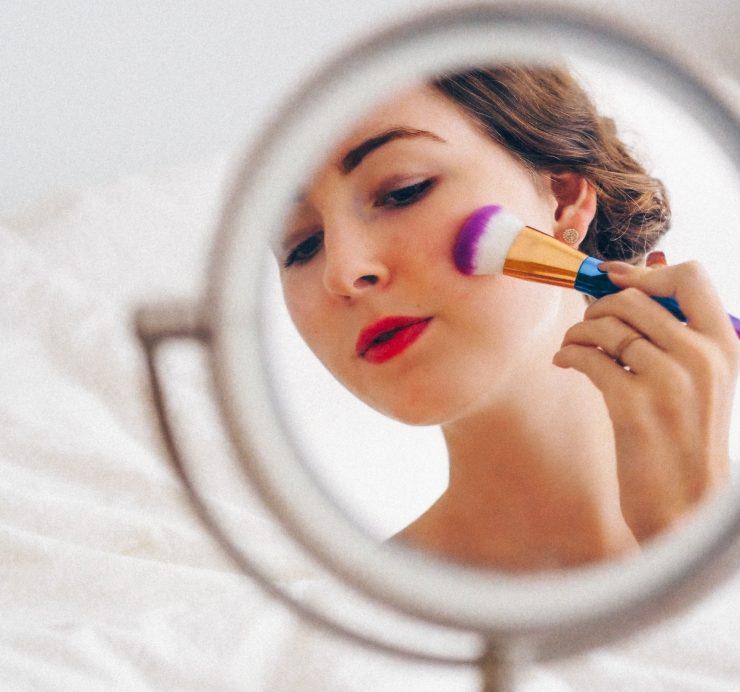 Mulher passando pincel de maquiagem no rosto