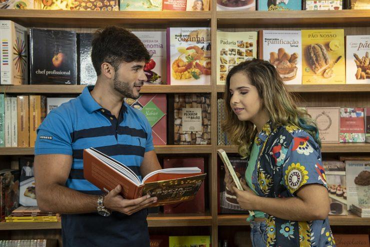 Homem e mulher dentro da livraria, abrindo livros