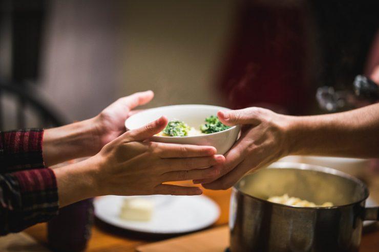 Mãos segurando prato de comida; livro reúne receitas vencedoras de concurso