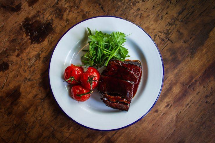 Tomates e filé em um prato branco; confira receita com filé mignon