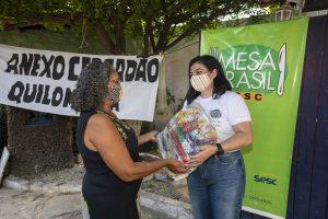 """Retrospectiva Mesa Brasil: na imagem, uma mulher entrega uma cesta básica para outra. Ambas usam máscaras de tecido. Atrás, há um cartaz onde se lê """"Mesa Brasil"""""""