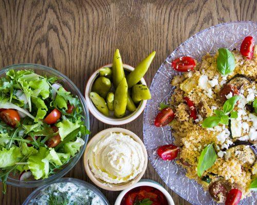 Cuscuz: na imagem, à direita, um prato de cuscuz marroquino. À esquerda, há vários potinhos com saladas e molhos.