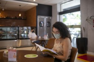 Livraria Senac Ceará: na imagem, uma mulher branca com cabelo cacheado castanho folheia um livro em uma mesa. Ela usa óculos e máscara de proteção.