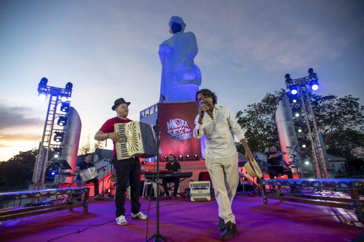 """Retrospectiva Sesc Ceará: na imagem, três músicos se apresentam em um palco armado em frente a estátua de Padre Cícero, em Juazeiro do Norte. O cantor usa calça e camisa social brancas, o sanfoneiro uma calça preta, camisa vermelha e chapéu preto; ao fundo, um tecladista está vestido de preto em frente a um cartaz vermelho onde se lê """"Mostra Sesc de Culturas""""."""