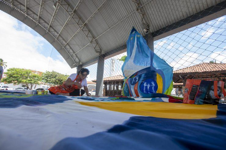Exposição no mar: Uma mulher pinta, em segundo plano, um tecido com cores azuis e branca. Ela usa uma camisa branca e um avental laranja e parece estar em uma quadra esportiva.