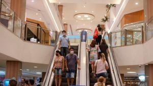 Expectativas para 2021: na imagem, duas escadas rolantes de um shopping estão cheias de clientes subindo (à direita) e descendo (à esquerda). Os clientes usam máscara e usam roupas coloridas.