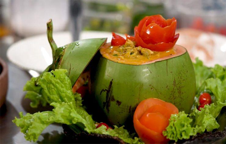 Receitas tradicionais: na imagem, um coco verde está em cima de folhas de alface e rodeado por tomates.