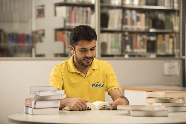 """Na imagem, um homem está sentado em frente a uma mesa cheia de livros, lendo um exemplar. Ele possui cabelo e barba curtos e pretos e usa uma camisa amarela onde se lê o nome """"Sesc"""", escrito em azul."""