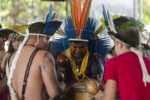 Povos tradicionais do Ceará: na imagem, três homens índigenas utilizam cocares coloridos e batem tambor juntos, em uma roda.