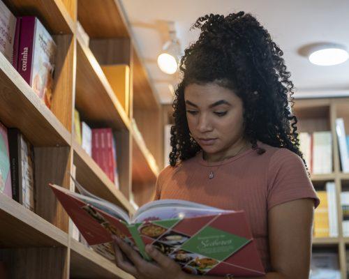 Bazar de Natal: na imagem, uma mulher jovem segura um livro aberto ao lado de uma estante. Ela é negra, tem cabelo preto, cacheado e preso em um coque e usa uma camisa marrom clara de manga curta.