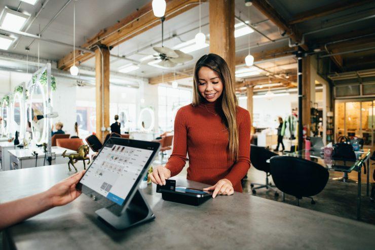 LGPD: na imagem, uma mulher de camisa vermelha e cabelos longos e lisos castanhos passa um cartão de crédito em uma maquineta em frente a um monitor.