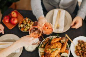 Ceias de Natal: a imagem mostra duas mãos brindando taças de vinho rosé. Embaixo há uma mesa onde se pode ver um peru e alguns outros pratos em segundo plano.