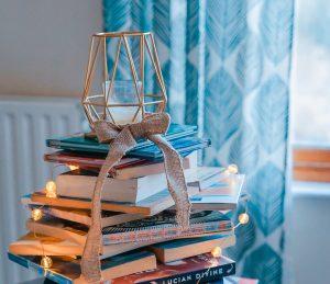Bazar de Natal: Na imagem, vários livros estão empilhados com luzinhas de Natal ao redor, formando uma espécie de árvore improvisada.