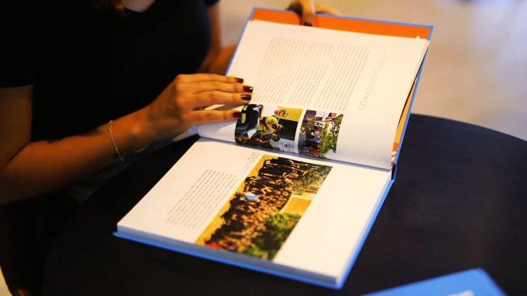 Mão feminina passando páginas de livro da CasaCor