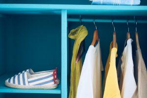 Guarda-roupa cápsula: a imagem mostra um guarda-roupa da cor azul com um sapato azul e branco (listrado) cinco camisas coloridas.