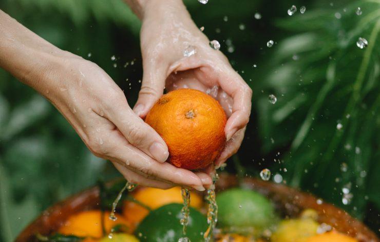 Mãos de mulher lavando laranja; forma correta de manipular alimentos é essencial
