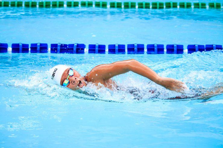 Homem nadando em piscina olímpica; confira onde praticar atividades físicas