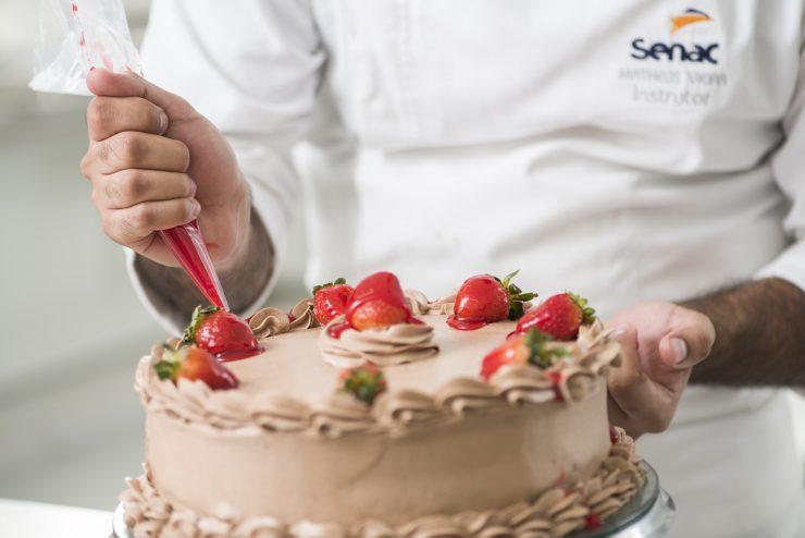 Homem com farda do Senac colocando cobertura em bolo; doces e guloseimas são dicas de renda extra