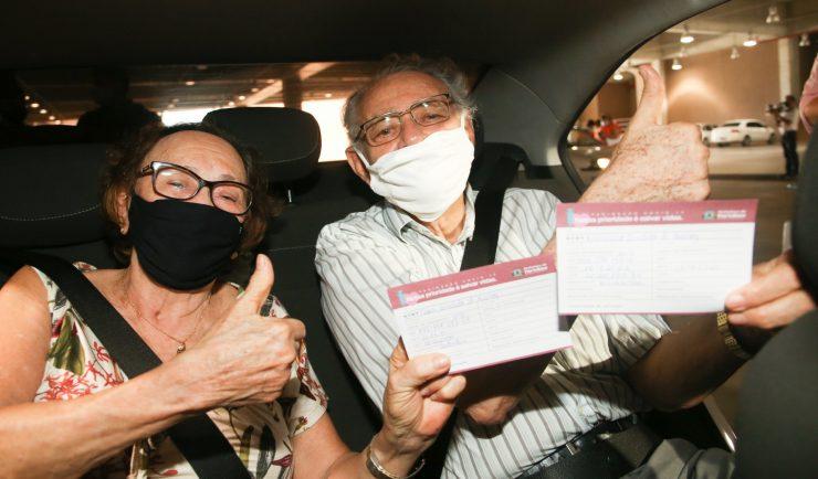 """Vacinação ganha apoio do Sistema Fecomércio: na imagem, um casal de idosos está dentro de um carro, com máscaras e óculos, mostrando suas carteirinhas de vacinação. Eles estão com os punhos fechados e polegares pra cima, em sinal de """"joinha""""."""